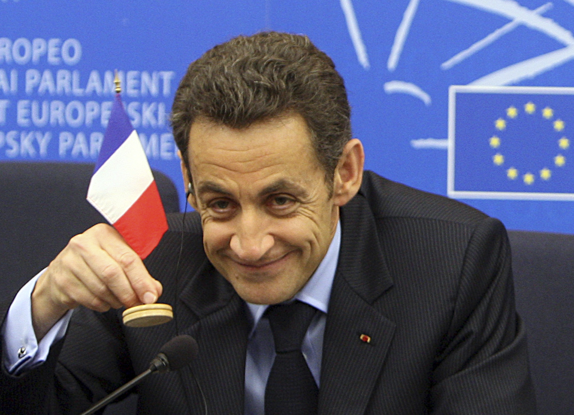 French President Nicolas Sarkozy holds a French flag during a press conference Tuesday Dec 16, 2008 at the European Parliament in Strasbourg, eastern France, after he made final appearance at European Parliament as his presidency of the European Union comes to an end. (AP Photo/Christian Lutz)